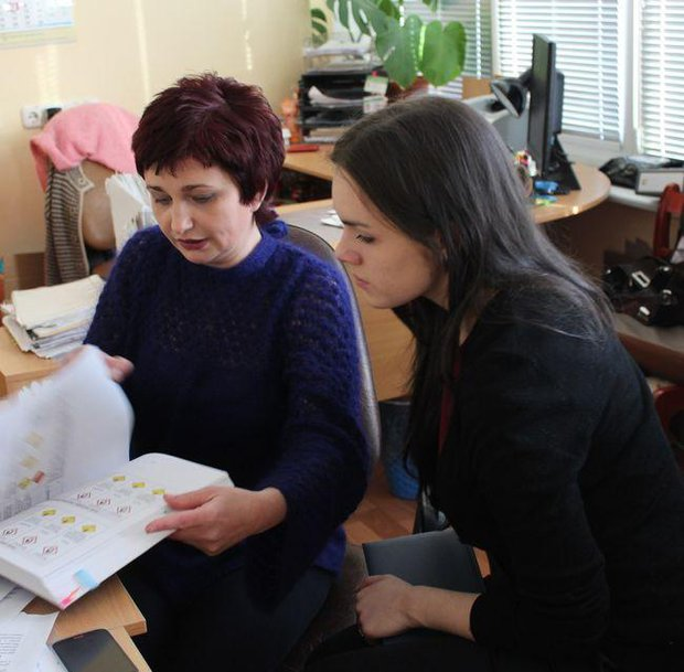 Светлана Петрова за столом с книгой