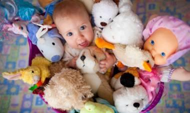 Ребенок лежит в куче игрушек
